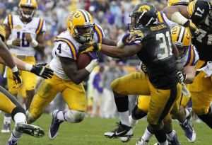 Jan 1, 2014; Tampa, Fl, USA; LSU Tigers running back Alfred Blue (4) stiff arms Iowa Hawkeyes linebacker Anthony Hitchens (31) during the first half at Raymond James Stadium. Mandatory Credit: Kim Klement-USA TODAY Sports