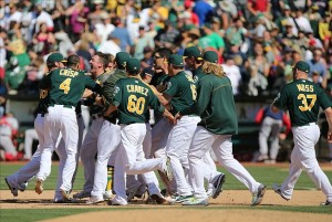 Jul 14, 2013; Oakland, CA, USA; Oakland Athletics surround third baseman Josh Donaldson (20) after hitting an RBI single for a walk-off win against the Boston Red Sox at O.co Coliseum. The Oakland Athletics debated the Boston Red Sox 3-2 in eleven innings. Mandatory Credit: Kelley L Cox-USA TODAY Sports