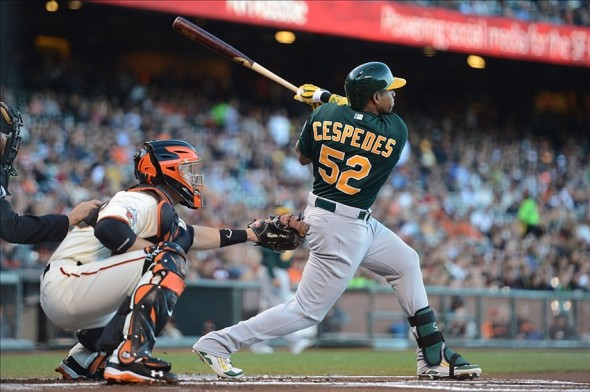 May 29, 2013; San Francisco, CA, USA; Oakland Athletics left fielder Yoenis Cespedes (52, right) hits a RBI-triple to score center fielder Coco Crisp (4, not pictured) in front of San Francisco Giants catcher Buster Posey (28, left) during the first inning at AT