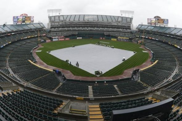 March 31, 2014; Oakland, CA, USA; General view of O.co Coliseum with the tarp on the field in rain before an opening day baseball game between the Oakland Athletics and the Cleveland Indians. Mandatory Credit: Kyle Terada-USA TODAY Sports