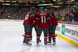 Mar 14, 2013; St. Paul, MN, USA; Minnesota Wild forward Zach Parise (11), forward Mikko Koivu (9) and defenseman Ryan Suter (20) celebrate a goal against the Colorado Avalanche at the Xcel Energy Center. The Wild defeated the Avalanche 5-3. Mandatory Credit: Brace Hemmelgarn-USA TODAY Sports