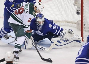 Oct 15, 2013; Toronto, Ontario, CAN; Minnesota Wild right wing Jason Pominville (29) tries to handle the puck in front of Toronto Maple Leafs goalie James Reimer (34) at the Air Canada Centre. The Maple Leafs beat the Wild 4-1. Mandatory Credit: Tom Szczerbowski-USA TODAY Sports