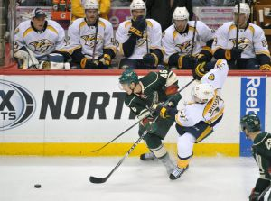 Minnesota Wild defenseman Jared Spurgeon battle for the puck along the boards with Predators forward Colin Wilson