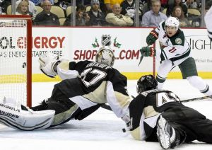Minnesota Wild leading goal scorer Zach Parise looks for another goal as Penguins try to block the shot in vain.