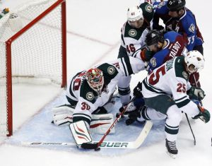 Minnesota Wild defensemen Jared Spurgeon and Jonas Brodin help clear the crease in game 1