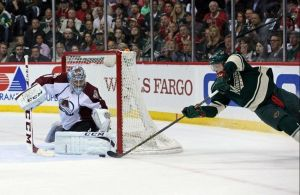 Minnesota Wild forward Charlie Coyle makes a diving shot on Colorado goalie Varlamov