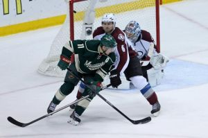 Minnesota Wild forward Zach Parise tips a puck past Colorado goalie Varlamov