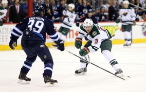 Minnesota Wild Assisstant Captain Zach Parise carries the puck up ice against the WINNIPEG jETS
