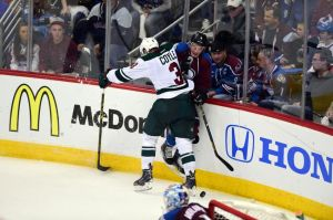 Minnesota Wild player Charlie Coyle makes a hit on an Avalanche player