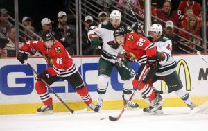 Minnesota Wild players try to stop a BlackHawk's line rush