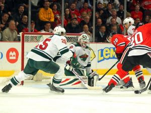 Minnesota Wild Goalie Ilya Bryzgalov tries to stop Blackhacks forward Ben Smith