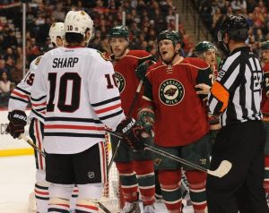 Minnesota WIld agitator Matt Cooke has a discussion with Patrick Sharp from Chicago