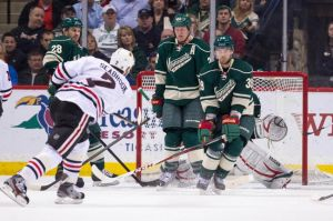 Minnesota Wild defenseman Nate Prosser blocks a shot against the Blackhawks along with Ryan Suter