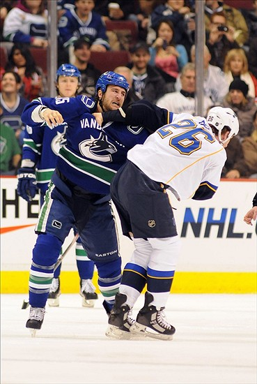 Feb 24, 2011; Vancouver, British Columbia, CANADA; St. Louis Blues forward BJ Crombeen (26) and Vancouver Canucks forward Tanner Glass (15) fight during the first period at Rogers Arena. Mandatory Credit: Anne-Marie Sorvin-US PRESSWIRE