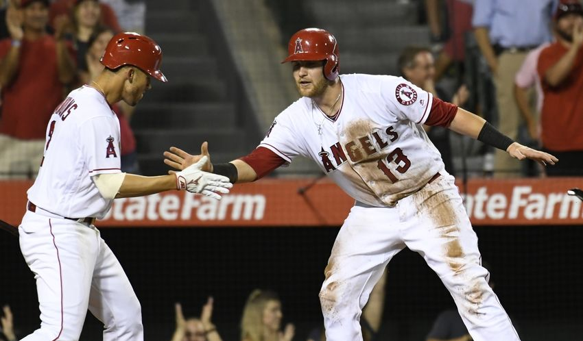 Aug 16, 2016; Anaheim, CA, USA;  Los Angeles Angels catcher Jett Bandy (13) celebrates scoring on a triple by second baseman Cliff Pennington (7) with shortstop Andrelton Simmons (2) against the Seattle Mariners during the eighth inning at Angel Stadium of Anaheim. Mandatory Credit: Richard Mackson-USA TODAY Sports