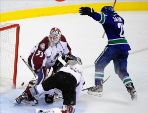 Dec 8, 2013; Vancouver, British Columbia, CAN; Vancouver Canucks forward Mike Santorelli (25) scores against Colorado Avalanche goaltender Jean-Sebastien Giguere (35) and defenseman Tyson Barrie (4) during the third period at Rogers Arena. The Vancouver Canucks won 3-1. Mandatory Credit: Anne-Marie Sorvin-USA TODAY Sports