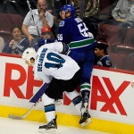 Sep 16, 2013; Vancouver, British Columbia, CAN; Vancouver Canucks defenseman Alex Biega (55) is checked into the boards by San Jose Sharks forward Andrew Desjardins (10) during the first period at Rogers Arena. Mandatory Credit: Anne-Marie Sorvin-USA TODAY Sports