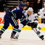Sep 16, 2013; Vancouver, British Columbia, CAN; San Jose Sharks forward Tommy Wingels (57) and Vancouver Canucks defenseman Yannick Weber (6) try to take possession of the puck during the second period at Rogers Arena. Mandatory Credit: Anne-Marie Sorvin-USA TODAY Sports