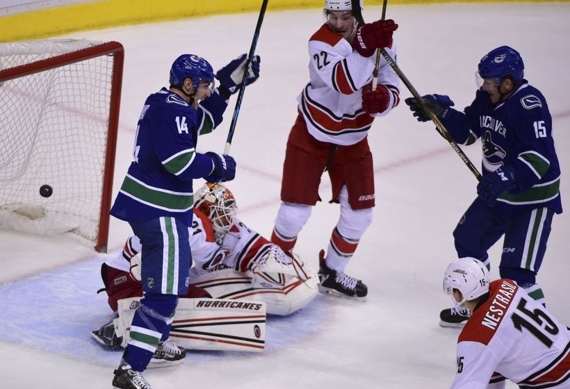 Oct 16, 2016; Vancouver, British Columbia, CAN; Vancouver Canucks forward Alexandre Burrows (14) and forward Derek Dorsett (15) celebrate defenseman Ben Hutton (27) goal against Carolina Hurricanes goaltender Eddie Lack (31) during the third period at Rogers Arena. The Vancouver Canucks won 4-3 in overtime. Mandatory Credit: Anne-Marie Sorvin-USA TODAY Sports