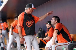 March 29, 2012; Tampa, FL, USA; Baltimore Orioles pitching coach Rick Adair (middle) talks with starting pitcher Jason Hammel (right) in the dugout against the New York Yankees at George M. Steinbrenner Field. Mandatory Credit: Kim Klement-US PRESSWIRE