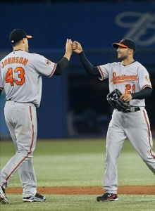 Apr 14, 2012; Toronto, ON, Canada; Baltimore Orioles right fielder Nick Markakis (21) celebrates the victory with pitcher Jim Johnson (43) against the Toronto Blue Jays at the Rogers Centre. The Orioles beat the Blue Jays 6-4. Mandatory Credit: Tom Szczerbowski-US PRESSWIRE