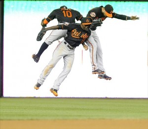 May 18, 2012; Washington, DC, USA; Baltimore Orioles teammates Nick Markakis (right), Xavier Avery (13) and Adam Jones (10) celebrate after defeating the Washington Nationals at Nationals Park. The Orioles defeated the Nationals 2-1. Mandatory Credit: Brad Mills-US PRESSWIRE