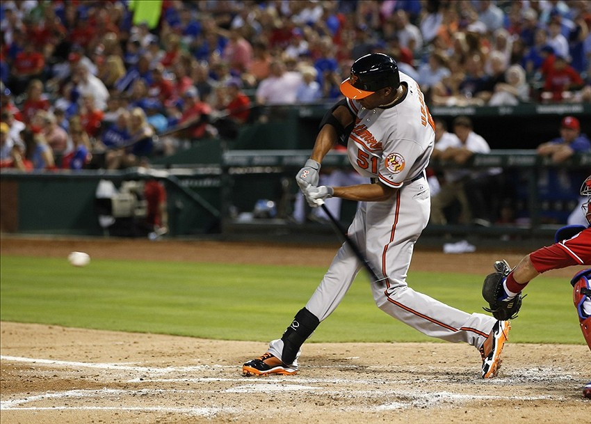 Jul 20, 2013; Arlington, TX, USA; Baltimore Orioles designated hitter Henry Urrutia (51) hits an RBI single against the Texas Rangers during the third inning at the Rangers Ballpark. Mandatory Credit: Jim Cowsert-USA TODAY Sports