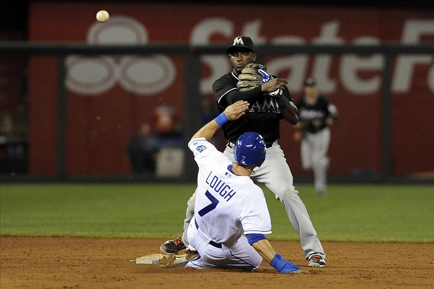 Aug 12, 2013; Kansas City, MO, USA; Miami Marlins shortstop Adeiny Hechavarria (3) turns a double play in the sixth inning against Kansas City Royals left fielder David Lough (7) at Kauffman Stadium. Mandatory Credit: John Rieger-USA TODAY Sports
