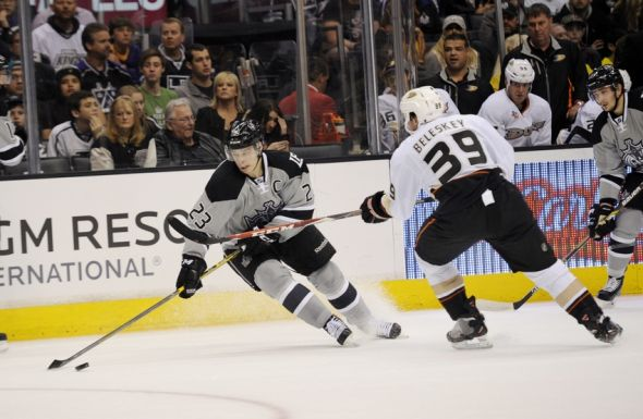 Apr 12, 2014; Los Angeles, CA, USA; Los Angeles Kings right wing Dustin Brown (23) moves the puck defended by Anaheim Ducks left wing Matt Beleskey (39) during the first period at Staples Center. Mandatory Credit: Kelvin Kuo-USA TODAY Sports