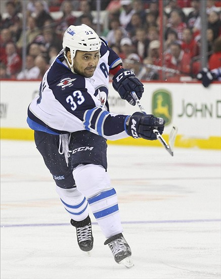 March 30, 2012; Raleigh, NC, USA; Winnipeg Jets defensemen Dustin Byfuglien (33) takes a slap shot against the Carolina Hurricanes at the PNC center. The Jets defeated the Hurricanes 4-3 in overtime. Mandatory Credit: James Guillory-US PRESSWIRE