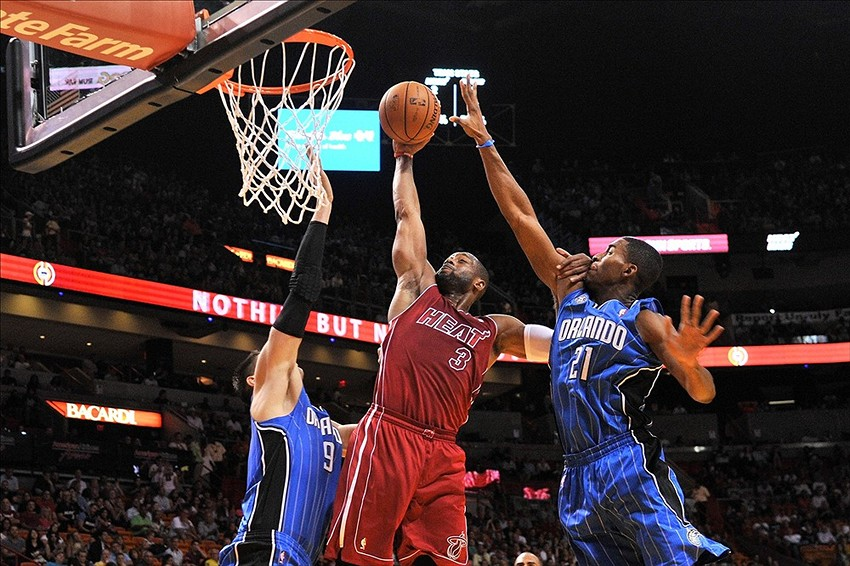 Nov 23, 2013; Miami, FL, USA; Miami Heat shooting guard Dwyane Wade (3) drives to the basket as Orlando Magic shooting guard Arron Afflalo (4) and Orlando Magic center Nikola Vucevic (9) defend at the basket during the second half at American Airlines Arena. The Heat won 101-99. Mandatory Credit: Steve Mitchell-USA TODAY Sports