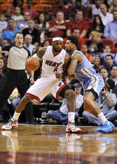 Mar 14, 2014; Miami, FL, USA; Miami Heat forward LeBron James (6) is pressured by Denver Nuggets forward Wilson Chandler (21) during the first half at American Airlines Arena. Mandatory Credit: Steve Mitchell-USA TODAY Sports