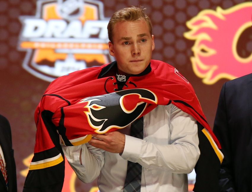 Jun 27, 2014; Philadelphia, PA, USA; Samuel Bennett puts on a team sweater after being selected as the number four overall pick to the Calgary Flames in the first round of the 2014 NHL Draft at Wells Fargo Center. Mandatory Credit: Bill Streicher-USA TODAY Sports