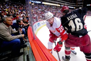 Mar. 25, 2013; Glendale, AZ, USA; Phoenix Coyotes defenseman Rostislav Klesla (16) checks Detroit Red Wings left wing Drew Miller (20) as fans watch during the second period at Jobing.com Arena. Mandatory Credit: Matt Kartozian-USA TODAY Sports