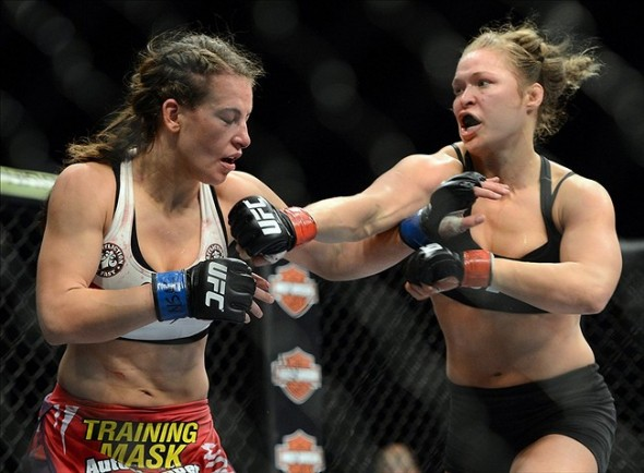 Dec 28, 2013; Las Vegas, NV, USA; Ronda Rousey (red gloves) and Miesha Tate (blue gloves) fight during their UFC women