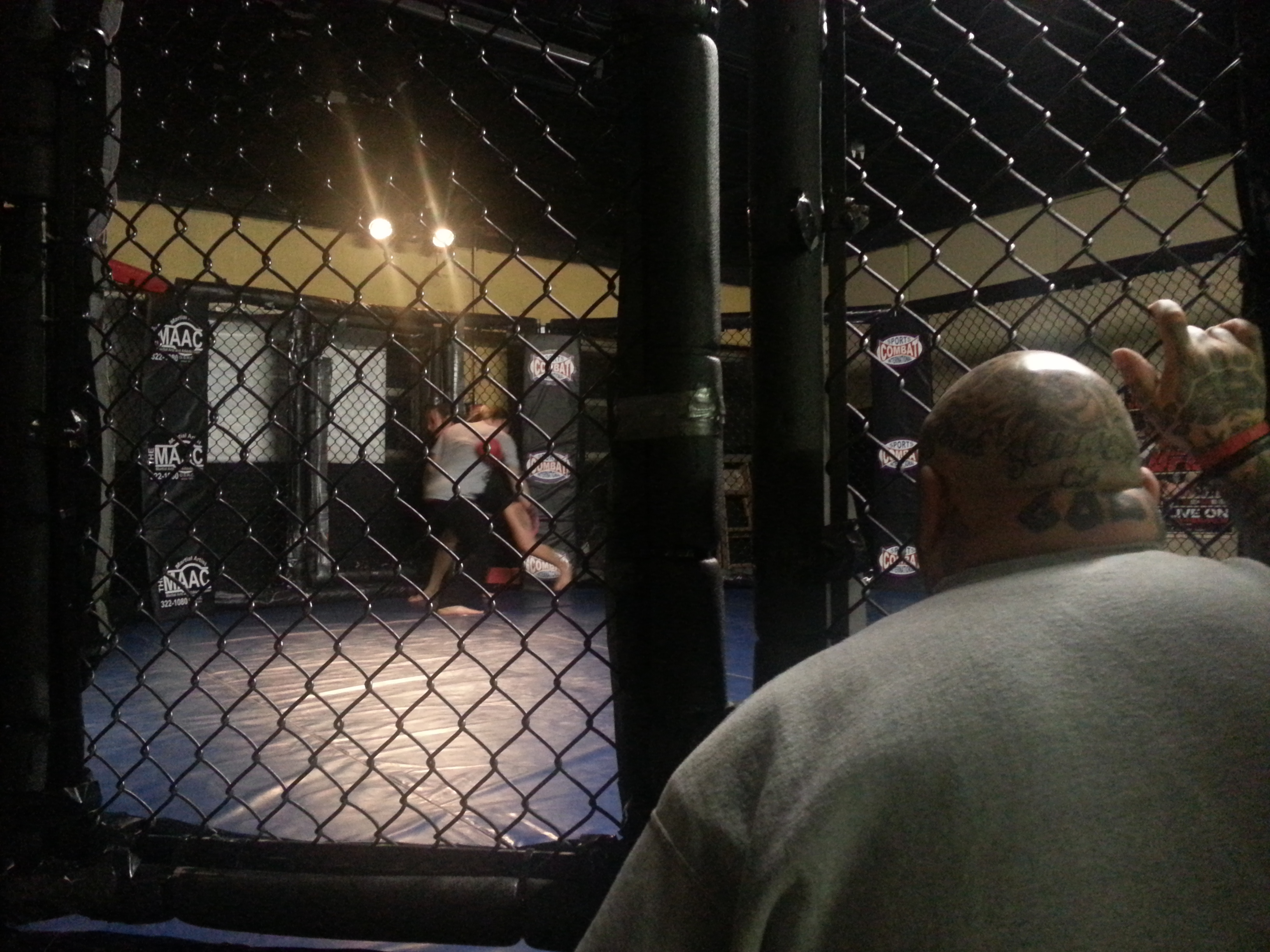 Coach Leon Aragon stands outside the cage as fighters Angel Jones and Katie McCord spar