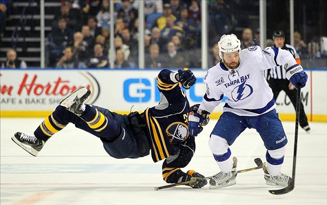Apr. 14, 2013; Buffalo, NY, USA; Tampa Bay Lightning defenseman Radko Gudas (75) checks Buffalo Sabres defenseman Adam Pardy (27) during the first period at First Niagara Center. Mandatory Credit: Timothy T. Ludwig-USA TODAY Sports