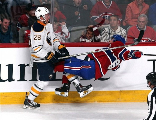 Sep 15, 2013; Montreal, Quebec, CAN; Montreal Canadiens defenseman Raphael Diaz (61) is checked by Buffalo Sabres center Zemgus Girgensons (28) during the first period at Bell Centre. Mandatory Credit: Jean-Yves Ahern-USA TODAY Sports