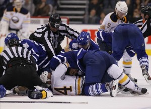Sep 22, 2013; Toronto, Ontario, CAN; Linesman Derek Nansen (70) tries to break up a fight between the Buffalo Sabres and Toronto Maple Leafs during the third period at the Air Canada Centre. Toronto defeated Buffalo 5-3. Mandatory Credit: John E. Sokolowski-USA TODAY Sports