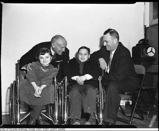 """Conn Smythe with children in wheelchairs"". From the City of Toronto Archives, retrieved from Flickr's Creative Commons."