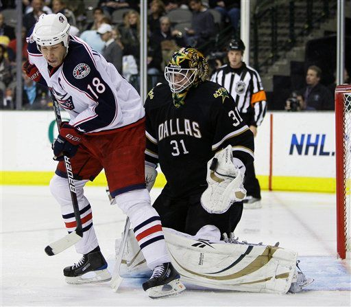 Alex Auld blocks a shot on goal with his glove as Columbus Blue Jackets center R.J. Umberger attempts to block his view. (AP Photo/Tony Gutierrez)