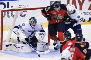 Dec 23, 2013; Sunrise, FL, USA; Tampa Bay Lightning goalie Ben Bishop (30) stops a shot as defenseman Jean-Philippe Cote (22) checks Florida Panthers left wing Tomas Kopecky (82) in the third period at BB