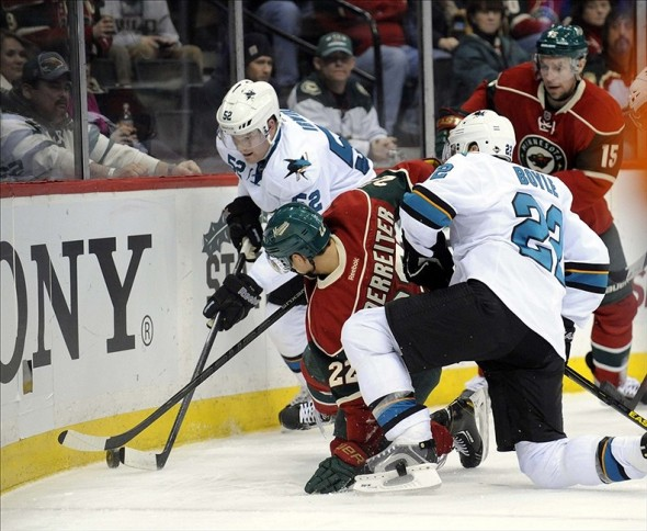 Dec 8, 2013; Saint Paul, MN, USA; San Jose Sharks defenseman Matt Irwin (52) and Minnesota Wild forward Nino Niederreiter (22) battle for the puck behind the Sharks net in the second period at Xcel Energy Center. Mandatory Credit: Marilyn Indahl-USA TODAY Sports