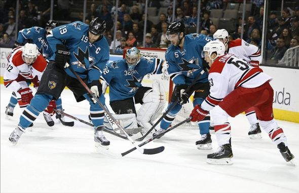 Mar 4, 2014; San Jose, CA, USA; San Jose Sharks center Joe Thornton (19) defends the San Jose Sharks goal in front of San Jose Sharks goalie Alex Stalock (32) during the first period against the Carolina Hurricanes at SAP Center at San Jose. Mandatory Credit: Bob Stanton-USA TODAY Sports