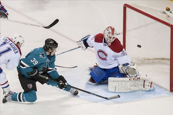 Mar 8, 2014; San Jose, CA, USA; San Jose Sharks center Logan Couture (39) shoots and scores against Montreal Canadiens goalie Dustin Tokarski (35) during the third period at SAP Center at San Jose. The San Jose Sharks defeated the Montreal Canadiens 4-0. Mandatory Credit: Ed Szczepanski-USA TODAY Sports