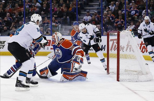 Mar 25, 2014; Edmonton, Alberta, CAN; San Jose Sharks forward Joe Pavelski (8) scores on Edmonton Oilers goaltender Ben Scrivens (30) during the during the second period at Rexall Place. Mandatory Credit: Perry Nelson-USA TODAY Sports