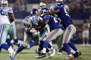 Sep 8, 2013; Arlington, TX, USA; Dallas Cowboys wide receiver Dez Bryant (88) is tackled by several members of the New York Giants defense in the second quarter of the game at AT
