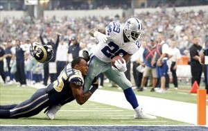 Sep 22, 2013; Arlington, TX, USA; Dallas Cowboys running back DeMarco Murray (29) scores a touchdown while being tackled by St. Louis Rams strong safety T.J. McDonald (25) in the second quarter of the game at AT