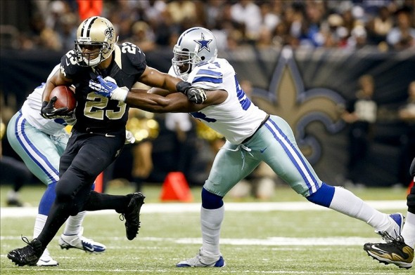 Nov 10, 2013; New Orleans, LA, USA; New Orleans Saints running back Pierre Thomas (23) breaks away from Dallas Cowboys defensive end DeMarcus Ware (94) during the first quarter of a game at Mercedes-Benz Superdome. Mandatory Credit: Derick E. Hingle-USA TODAY Sports