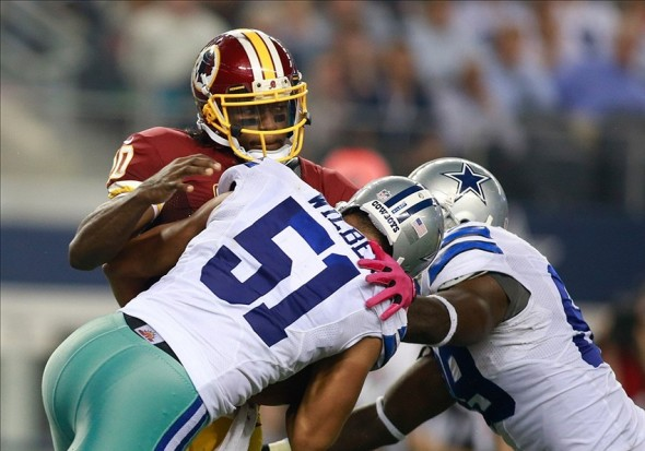 Oct 13, 2013; Arlington, TX, USA; Washington Redskins quarterback Robert Griffin III (10) is sacked by Dallas Cowboys defensive end Kyle Wilber (51) and defensive end George Selvie (99) at AT